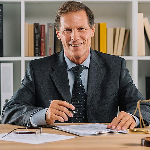 Advokat-mand-sidder-bag-skrivebord-logo