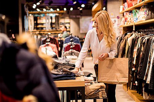 Tøjbutik-kvinde-smiler-og-shopper-banner