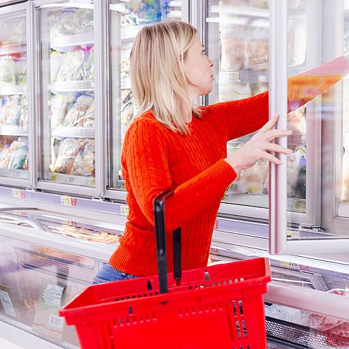 Detail Dagligvarer-kvinde-henter-varer-fra-køledisk logo