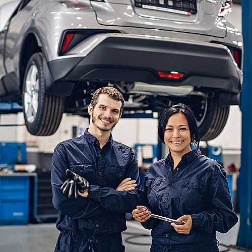 Biler-mekaniker-par-står-foran-bil-på-lift-logo