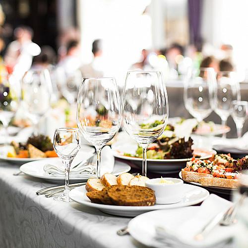 Restaurant-spisested-vinglas-på-et-rodet-bord-logo