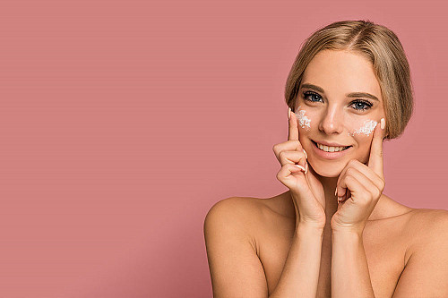 Hudpleje-kvinde-putter-cream-på-sit-ansigt-banner