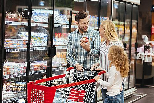 Detail Dagligvarer-familie-går-med-indkøbskurv-ved-kølediske-banner