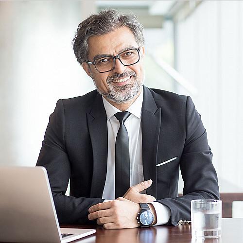 Advokat-mand-sidder-bag-skrivebord-med-briller logo